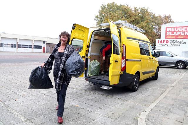 Wethouder Pastoor brengt bus vol kleren naar de Kledingbank